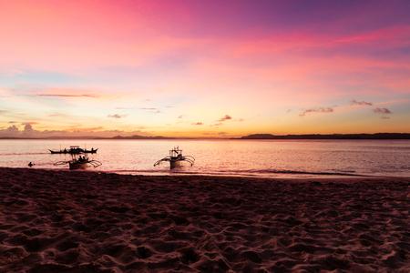 Traditionelle Fischerboote bei Sonnenuntergang am unberührten Strand, Philippinen Standard-Bild