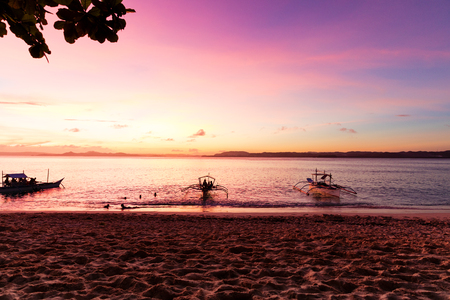 Traditional fishing boats at sunset on pristine beach,  Philippines Standard-Bild