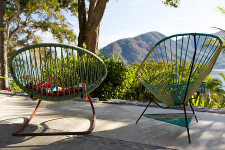 Traditional Mexican woven chairs overlooking rainforest, Jalisco, Mexico