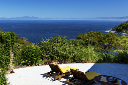 Sunbeds overlooking tropical rainforest and the bay of Puerto Vallarta, Jalisco, Mexico