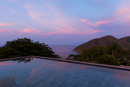Swimming pool at sunset overlooking tropical rainforest and the bay of Puerto Vallarta, Jalisco, Mexico