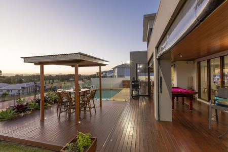 Backyard patio setting with swimming pool at sunset in luxury home Stock Photo
