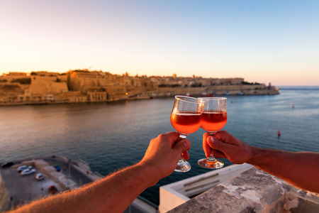 Cheers from Malta, sunset over Valletta with wine glasses Stock Photo