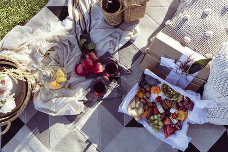 Romantic picnic set up with mixed food platter and wine at sunset