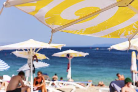 Mediterranean beach with tourists and beach umbrella, focus on umbrella