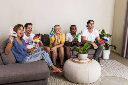 Group of young multinational sports fans cheering with flags watching TV from couch