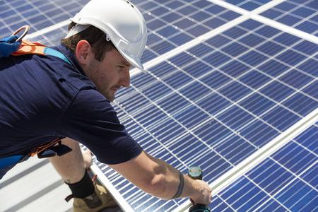 Técnico de paneles solares con taladro de instalación de paneles solares en el techo en un día soleado Foto de archivo