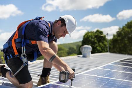 Technik paneli słonecznych z wiertłem instaluje panele słoneczne na dachu w słoneczny dzień Zdjęcie Seryjne