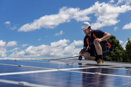Technik paneli słonecznych z wiertłem instaluje panele słoneczne na dachu w słoneczny dzień