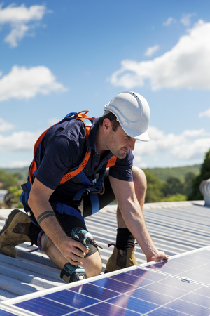 Tecnico del pannello solare con il trapano che installa i pannelli solari sul tetto un giorno soleggiato
