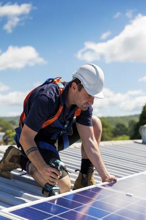 Técnico de paneles solares con taladro instalando paneles solares en el techo en un día soleado