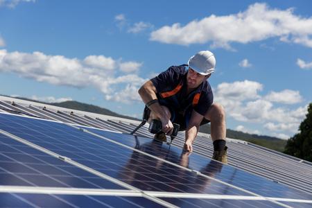 Technicien de panneaux solaires avec perceuse installer des panneaux solaires sur le toit par une journée ensoleillée
