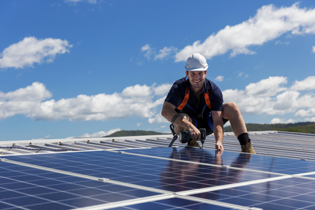 Solar panel technician with drill installing solar panels on roof on a sunny day 写真素材 - 99948747