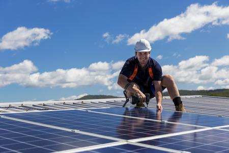 Technicien de panneaux solaires avec perceuse installer des panneaux solaires sur le toit par une journée ensoleillée Banque d'images