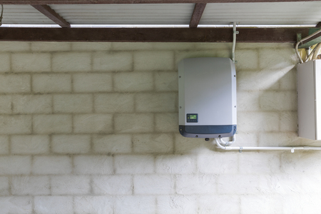 Solar power inverter mounted on brick wall inside garage, domestic system