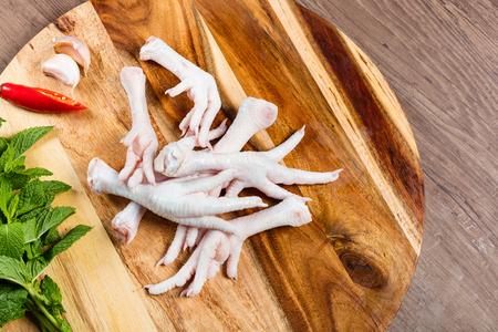 Patas de pollo crudo sobre una tabla de cortar con hierbas