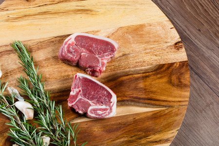 Raw lamb loin slices on chopping board with herbs