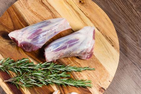 Raw lamb shanks on chopping board with herbs 版權商用圖片