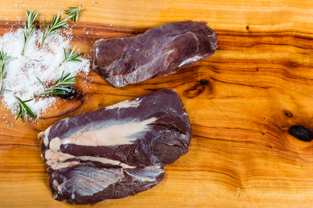 Raw emu meat slices on chopping board with herbs