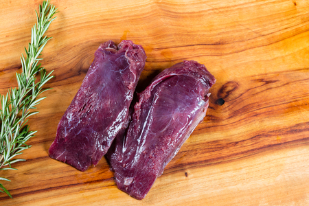 Raw kangaroo meat slices on chopping board with herbs