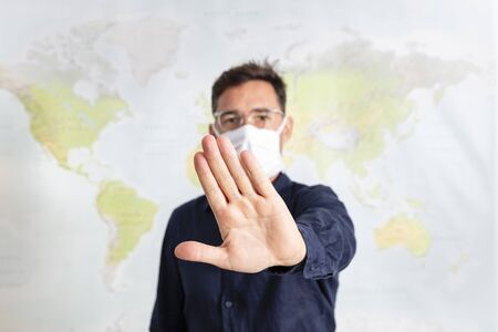 Man with face mask gesturing to keep away to avoid transmitting disease