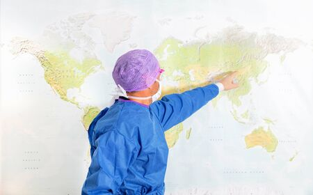 Doctor in a protective suit pointing at possible infection sources on world map