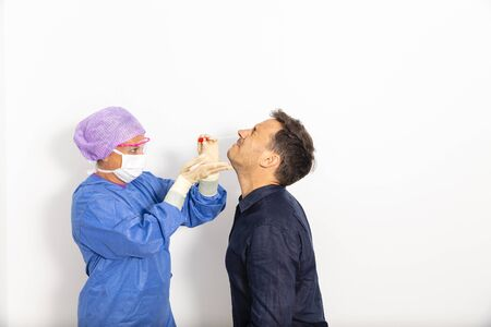 A doctor in a protective suit taking a nasal swab from a person to test for possible coronavirus infection Standard-Bild