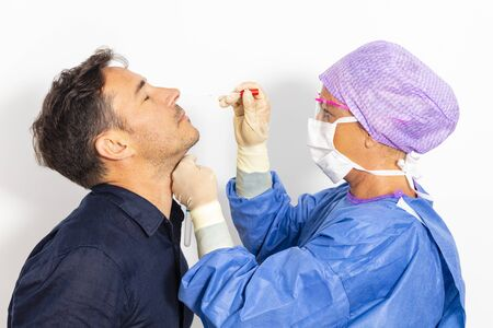 A doctor in a protective suit taking a nasal swab from a person to test for possible coronavirus infection Stock Photo