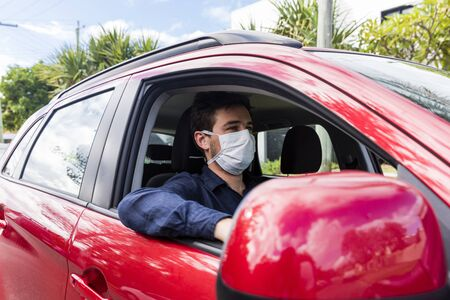 Young male driver inside car with protective face mask