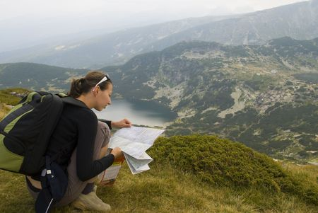 Resting mountaineer is reading a map. The picture was taken on the Seven Rila lakes in the Rila mountain, Bulgaria. photo