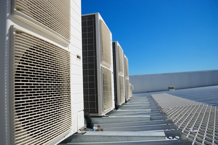 Air Conditioner units on the roof of an industrial building. Blue sky in the background. No people. Copy space. Stock Photo