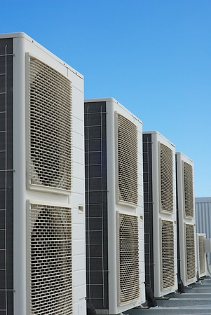Air Conditioner units on the roof of an industrial building. Blue sky in the background. No people. Copy space. Standard-Bild