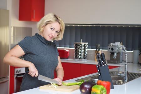 A woman in grey dress is preparing healthy dinner. photo