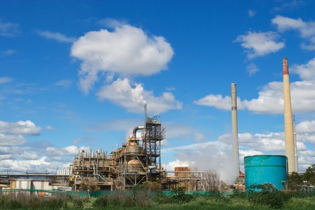 Old factory releasing white smoke in the blue sky. photo