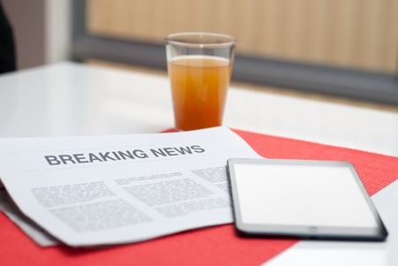 Breaking news article in a newspaper read at breakfast. photo