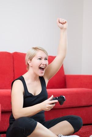 playing video games: Ganar chica rubia est� jugando juegos de video. Foto de archivo