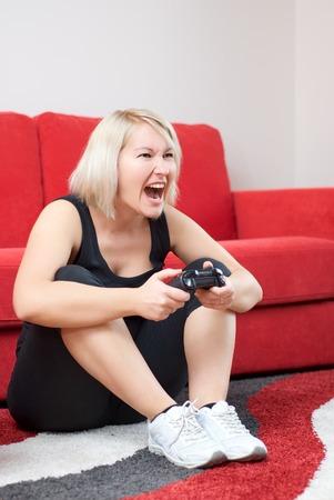 jugando videojuegos: Chica rubia est� enojada mientras que los juegos de video.