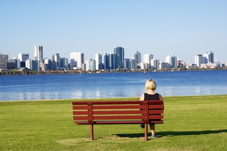 Woman sit on Red bench looking at the city of Perth photo