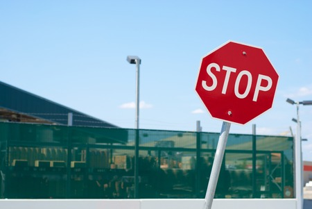 warning sign: Red stop sign in front of a warehouse fence Stock Photo