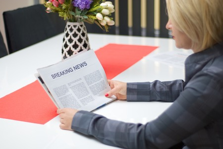 breaking news: Woman reading breaking news article in the newspaper at home.
