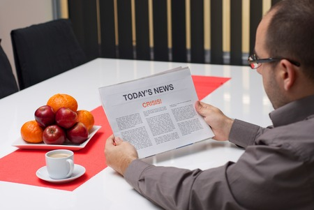 Man reading crisis article in the newspaper at home. photo