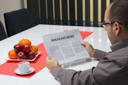 Man reading breaking news article in the newspaper at home. photo