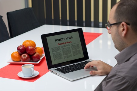 breaking news: Man reading breaking news article on the laptop at home.