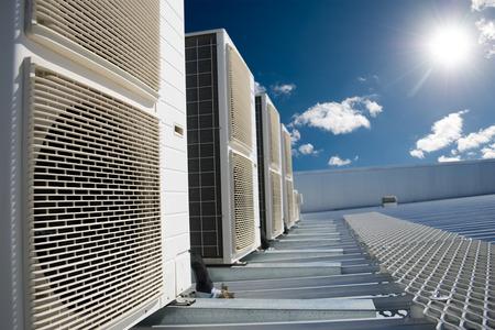 Airco units op een dak van een industrieel gebouw met blauwe hemel en wolken op de achtergrond.