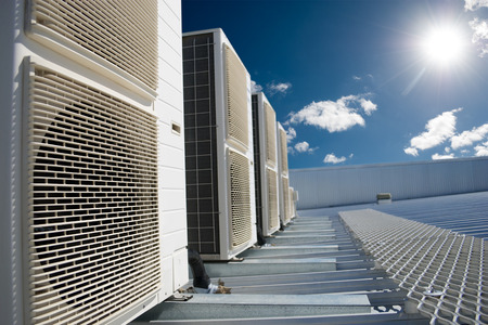 bedrijfshal: Airco units op een dak van een industrieel gebouw met blauwe hemel en wolken op de achtergrond.