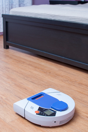 Vacuum robot cleaning timber floor.