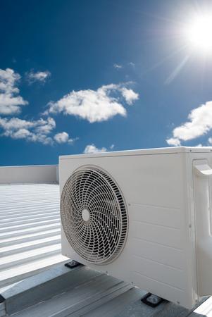 compresor: Blanca unidad de aire acondicionado en un tejado de metal industrial. Foto de archivo