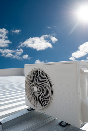 White air conditioning unit on a metal industrial roof.
