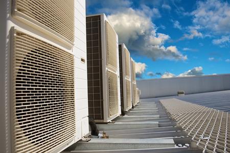 compresor: Unidades de aire acondicionado en un tejado de metal industrial de la tarde Foto de archivo