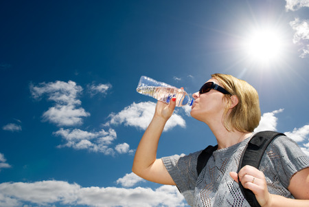 Blonde female tourist drinking water from a plastic bottle Standard-Bild
